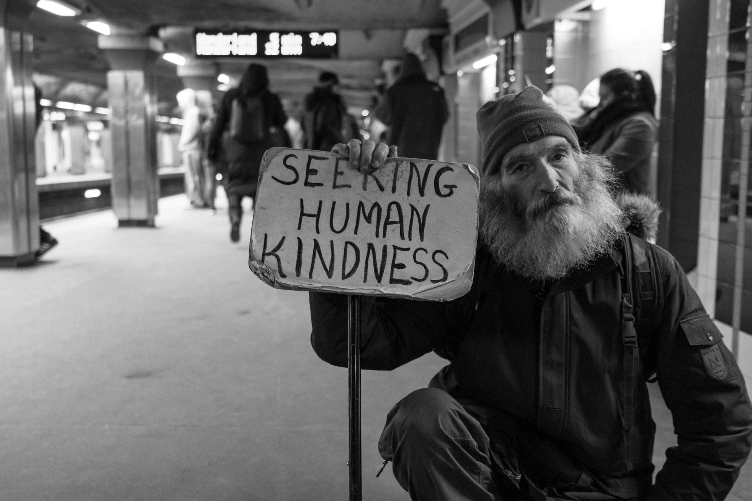 "Homeless man with a sign that says ""Seeking human kindness"""